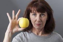 Unglückliche 50s reifen die Frau, die den Geschmack des goldenen Apfels in Frage stellt Lizenzfreies Stockfoto