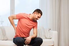 Unglücklicher Mann, der zu Hause unter Rückenschmerzen leidet Stockbilder