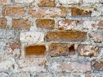Ungleiche Wand des roten Backsteins des Weinleseschmutzes mit besprühtem weißem Gipsbeschaffenheitshintergrund Stockbild