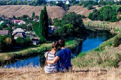 Ungt älska parsammanträde i kram på överkanten av en kulle med den underbara sikten av floden Arkivfoton