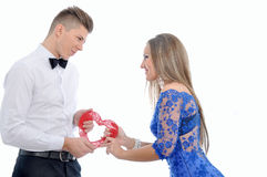 Ungt älskvärt kopplar ihop hållande röd hjärta tillsammans Fotografering för Bildbyråer