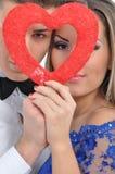 Ungt älskvärt kopplar ihop hållande röd hjärta tillsammans Royaltyfri Bild