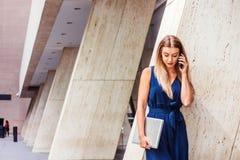 Ungt östligt - europeisk amerikansk kvinna som talar på mobiltelefonouts royaltyfria foton