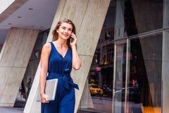 Ungt östligt - europeisk amerikansk kvinna som talar på telefonen, travelin royaltyfri foto