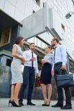 Ungt affärsfolk som talar med modern kontorsbyggnad Arkivbild