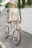 Ungt affärskvinnaanseende med cykeln Fotografering för Bildbyråer