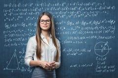 Ungt affärskvinnaanseende på bakgrunden av svart tavla med matematiska formler Royaltyfri Fotografi