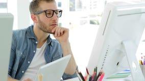 Ungt affärskvinnaarbete som koncentreras på hans skrivbord arkivfilmer