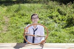 Ungt affärskvinnasammanträde bak hjulet av en imaginär ca Fotografering för Bildbyråer