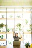 Ungt affärskvinnasammanträde på ett kontorsskrivbord framme av bärbara datorn med henne händer upp Arkivfoton