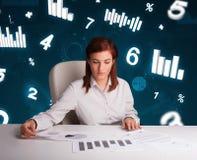 Ungt affärskvinnasammanträde på skrivbordet med diagram och statistik arkivfoto