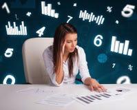 Ungt affärskvinnasammanträde på skrivbordet med diagram och statistik fotografering för bildbyråer