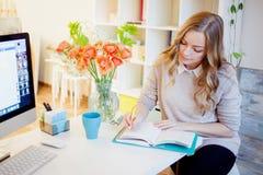 Ungt affärskvinnasammanträde på skrivbordet och arbete Den härliga kvinnan fyller stadsplaneraren royaltyfri bild