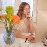 Ungt affärskvinnasammanträde på skrivbordet och arbete Härlig kvinna och hennes arbetsplats Fotografering för Bildbyråer