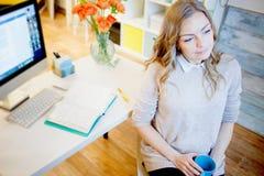 Ungt affärskvinnasammanträde på skrivbordet och arbete vart härligt ändrande inramnintt dricka för kaffe har bilder min fotoportf Royaltyfri Bild