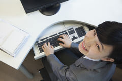 Ungt affärskvinnasammanträde på skrivbordet som ser le upp Royaltyfri Foto