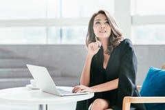 Ungt affärskvinnasammanträde på stolen med hennes labtop Arkivbild