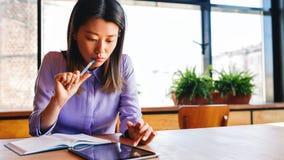 Ungt affärskvinnasammanträde på tabellen och se skärmen av det digitalt royaltyfri bild