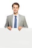 Ungt affärsmananseende med en tom whiteboard som isoleras royaltyfria foton