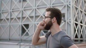 Ungt affärsmananseende nära det moderna kontoret och samtal med någon Den stilfulla mannen använder smartphonen till att kalla lager videofilmer