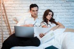 Ungt affärsmansammanträde i säng som arbetar på bärbara datorn Mannen studerar dokument royaltyfri foto