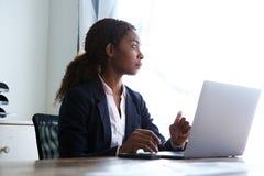 Ungt afrikanskt affärskvinnasammanträde på hennes skrivbord med en bärbar dator royaltyfria foton