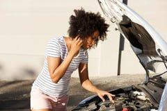 Ungt afrikanskt kvinnaanseende med den brutna ner bilen som parkeras på vägen och att kalla för hjälp arkivfoton