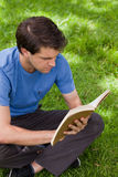 Ungt allvarligt mansammanträde arg-lade benen på ryggen stundläsning en boka Arkivbilder