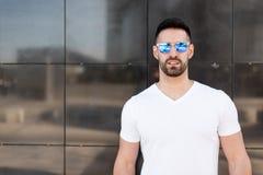 Ungt amerikanskt le för man som är lyckligt med den utomhus- solglasögonståenden Arkivbild