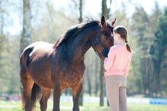 Ungt anseende för tonårs- flicka med hennes favorit- kastanjebruna häst royaltyfria foton