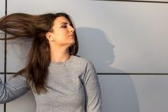 Ungt anseende för tonårs- flicka mot den gråa väggen med kopieringsutrymme Arkivbild