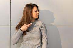 Ungt anseende för tonårs- flicka mot den gråa väggen med kopieringsutrymme Royaltyfri Foto