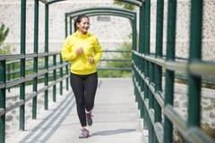 Ungt asiatiskt öva för kvinna som är utomhus- i det gula neonomslaget som joggar Arkivbild