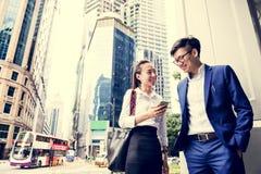 Ungt asiatiskt affärsfolk i en stad arkivbild