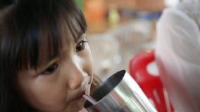 Ungt asiatiskt barn som dricker ett exponeringsglas av vatten stock video