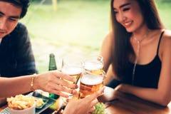 Ungt asiatiskt folk som har gyckel på att dricka med bifall med biet royaltyfri fotografi