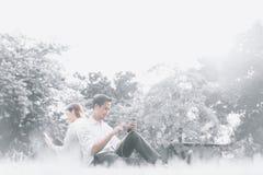 Ungt asiatiskt högskolestudentparsammanträde och koppla av tillsammans i parkera och att lyssna till musik på smartphones Fotografering för Bildbyråer