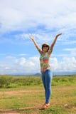 Ungt asiatiskt kvinnaanseende i fält och stigning upp hennes hand med trevlig sinnesrörelse arkivbild
