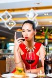 Ungt asiatiskt kvinnasammanträde i restaurang arkivbild
