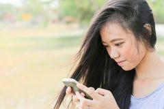 Ungt asiatiskt kvinnasammanträde i trädgård genom att använda en mobiltelefon arkivbild
