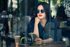Ungt asiatiskt kvinnasammanträde på en coffee shop som rymmer hennes smarta pho Arkivbilder