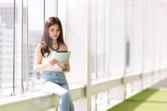 Ungt asiatiskt kvinnasammanträde på korridoren Royaltyfri Fotografi