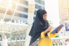 Ungt asiatiskt le för muslimaffärskvinna och dokument och anseende för hållande mapp på huvudstaden royaltyfri fotografi