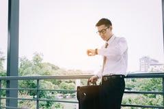 Ungt asiatiskt manligt anseende som kontrollerar tid och hållande portföljwi arkivbilder