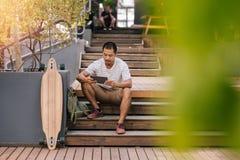 Ungt asiatiskt mansammanträde på utvändig trappa genom att använda en minnestavla Arkivfoto