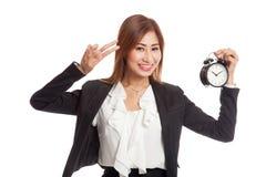 Ungt asiatiskt tecken för seger för show för affärskvinna med en klocka Arkivfoton