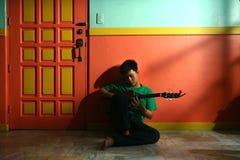 Ungt asiatiskt tonårigt spela gitarren i en vardagsrum Arkivfoton