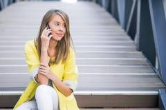 Ungt attraktivt affärskvinnasammanträde på bron och använda den smarta telefonen fotografering för bildbyråer