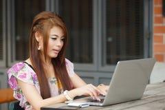 Ungt attraktivt affärskvinnaarbete på henne bärbar dator på utomhus- Arkivbild