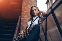Ungt attraktivt flickaanseende i den vita skjortan med en saxofon - som är utomhus- i gammal stad Sexig ung kvinna med saxofonen  Royaltyfria Foton
